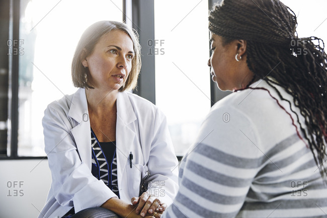 Mature female doctor talking while consoling patient in hospital