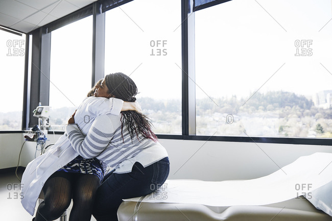 Mature female doctor embracing young patient while sitting on hospital bed