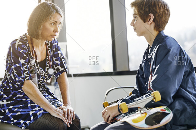 Mature female doctor talking with boy holding skateboard in hospital