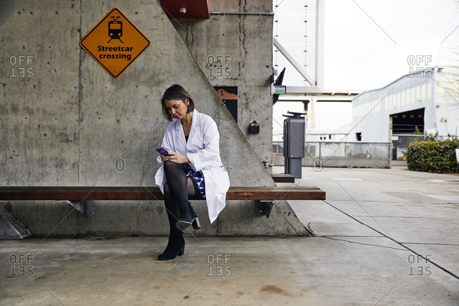 Female doctor using mobile phone while sitting on bench waiting for streetcar