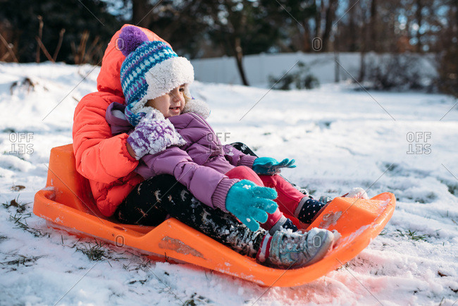 Children sledding in the snow with sun shining