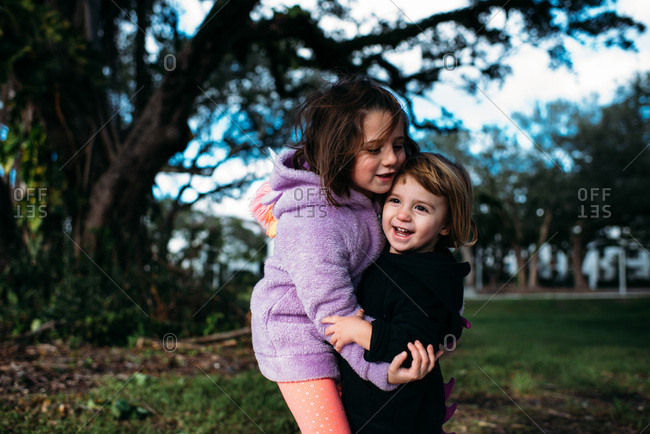 Sisters hugging each other outside in a park