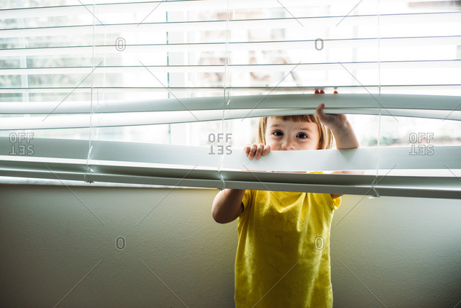 Toddler in yellow shirt playing with blinds