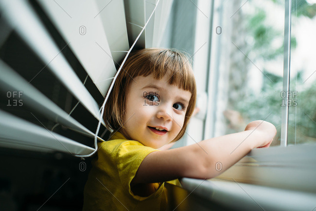 Toddler in yellow shirt playing near window