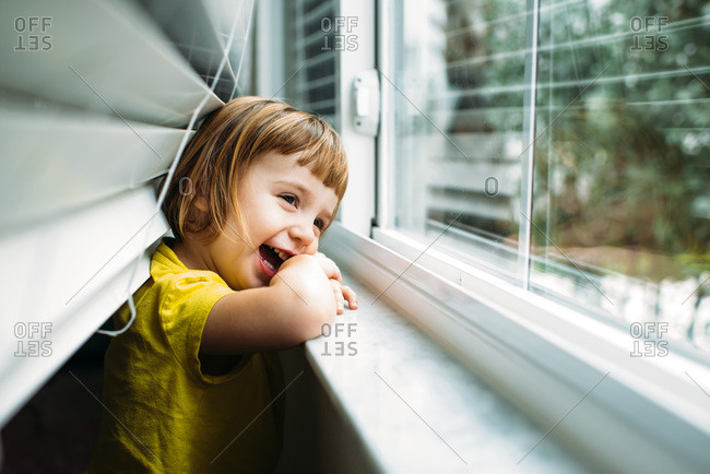 Toddler in yellow shirt looking out window