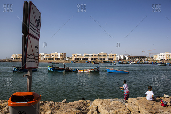 Bou Regreg, Morocco - August 6, 2013: Young boys fishing in Rabat
