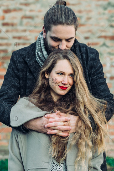 Portrait of beautiful young couple hugging and smiling looking in love