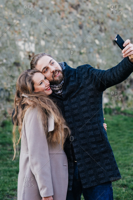 Beautiful couple hugging each other and making selfie photo with their phone camera