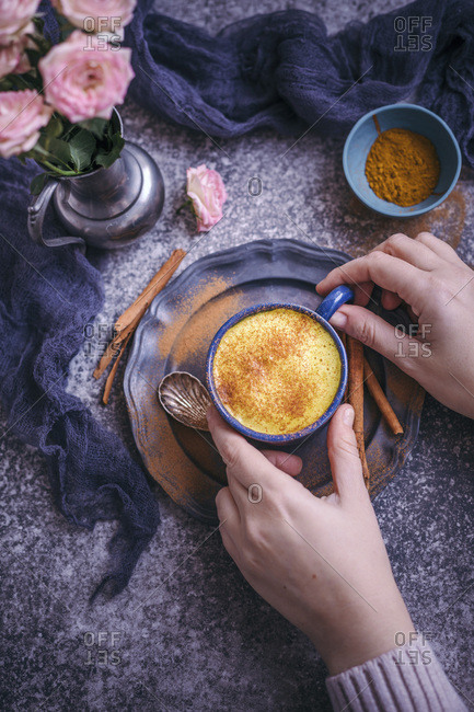 Woman drinking golden milk turmeric latte served in a blue cup