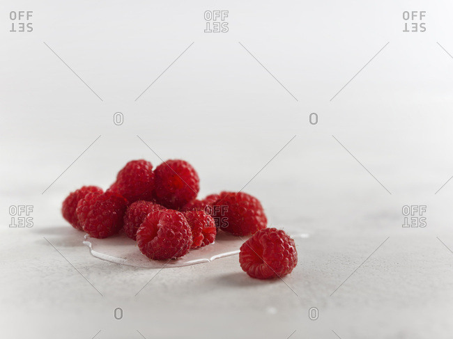 Macro shot of fresh raspberries in water on a white textured surface