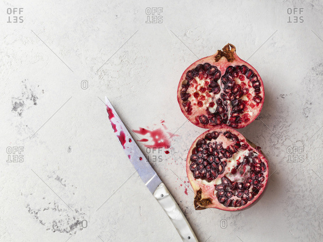 Cut pomegranate on a white textured surface with knife and spilled pomegranate juice