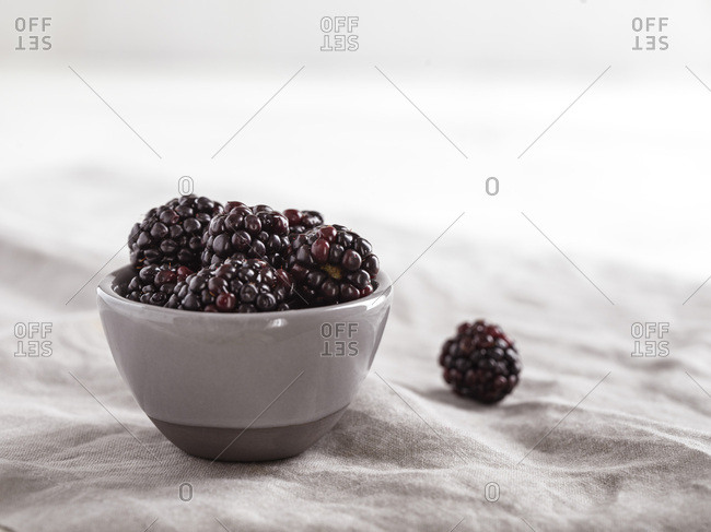 Small, gray bowl filled with fresh blackberries on a gray linen with a bright, airy background