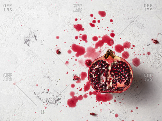 Half pomegranate on a white textured surface with pomegranate juice splashes