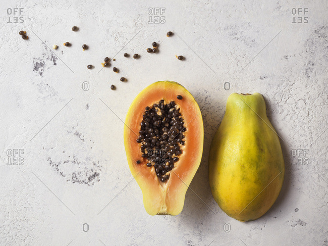 Papaya cut in half with seeds scattered around on a white textured surface