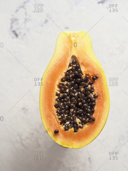 Single papaya cut in half to show flesh and seeds on bright white, textured background