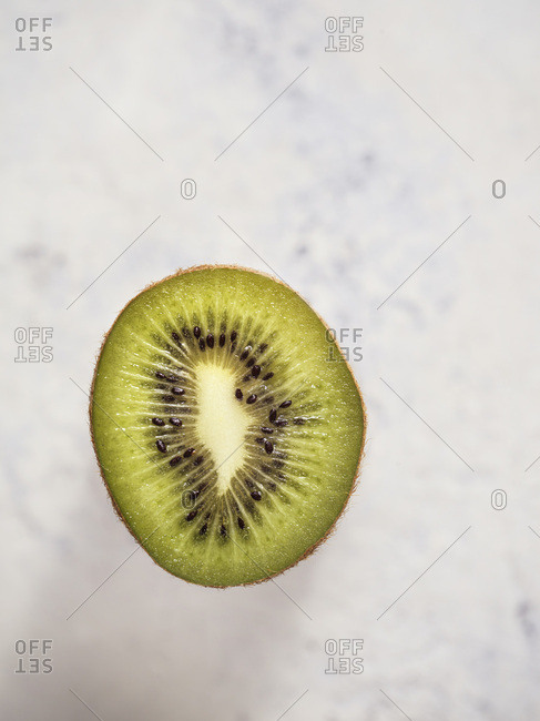 Half kiwi showing detail of flesh and seeds on a bright white, textured surface