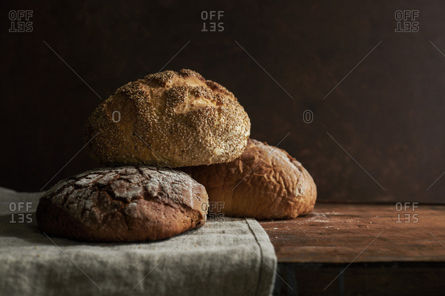 A variety of rustic bread loaves on a linen and a rich, wood surface