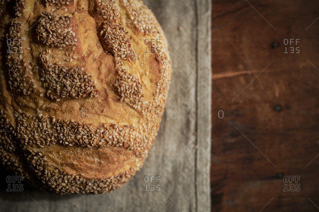 Round loaf or rustic sesame bread on a linen and rich, wood surface