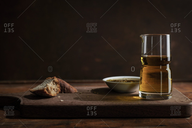 Broken chunks of rustic rye bread with dipping oil bowl and glass on a rich wood cutting board and surface
