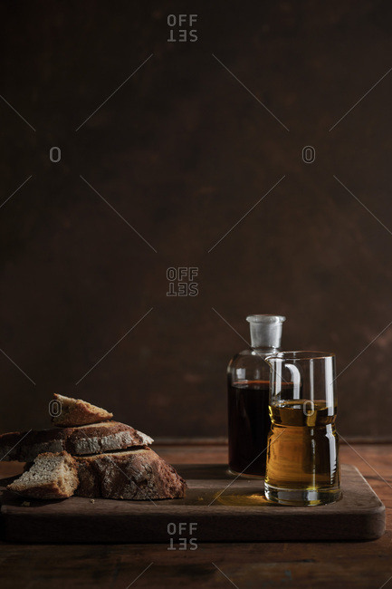 Chunks of rustic rye bread on a rich wood surface with antique bottles of oil and vinegar