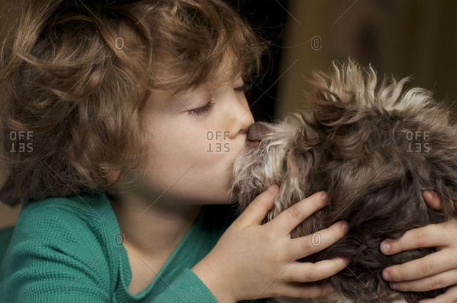 Boy kissing dog on the lips