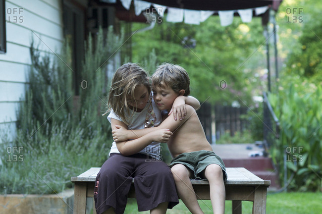 Two children sitting on an outdoor table hugging