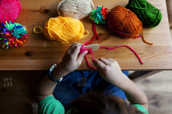 Overhead view of young boy's hands making a pompom