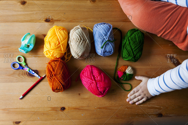 Overhead view of colorful balls of yarn and other materials for making pompoms