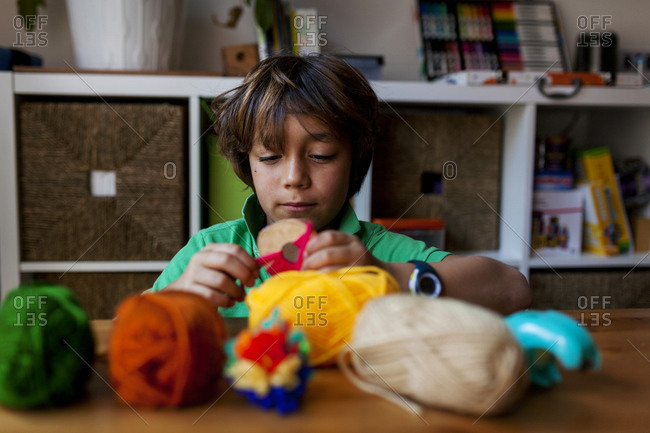 Young boy making pompom with colorful balls of yarn in the foreground