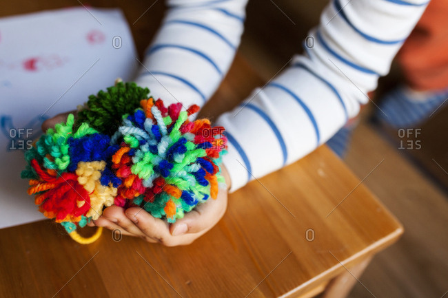 Pair of kid's hands showing off completed colorful pompoms