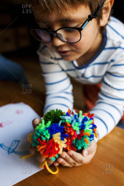 Young boy with glasses holding out the colorful pompoms he has just made
