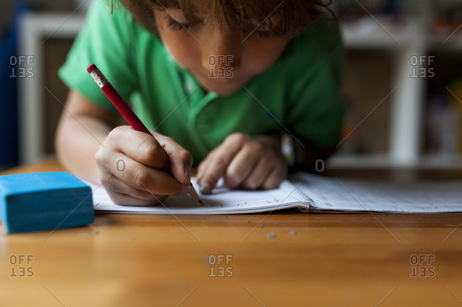 Young boy diligently working on music home work