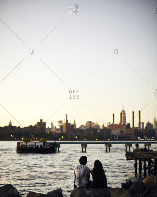 Couple sitting together along riverbank looking at the New York City skyline at sunset