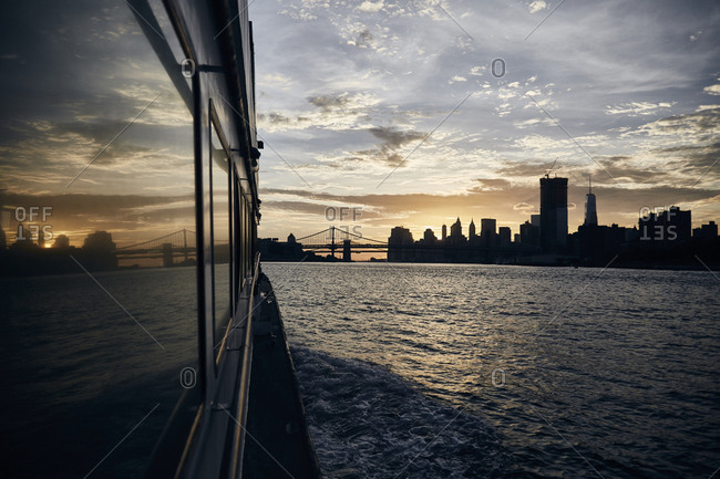 Silhouette of New York City skyline at sunset reflected in window of ferry