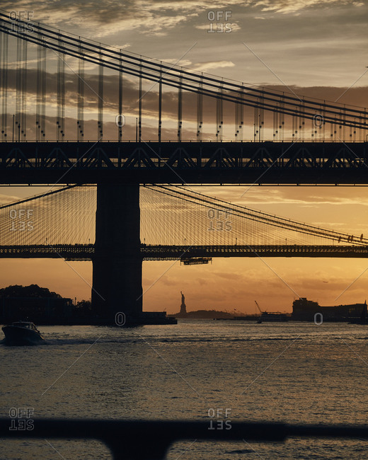 Silhouette of suspension bridges in New York City from ferry