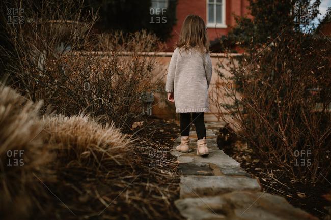 Back view of little girl walking along stone garden path