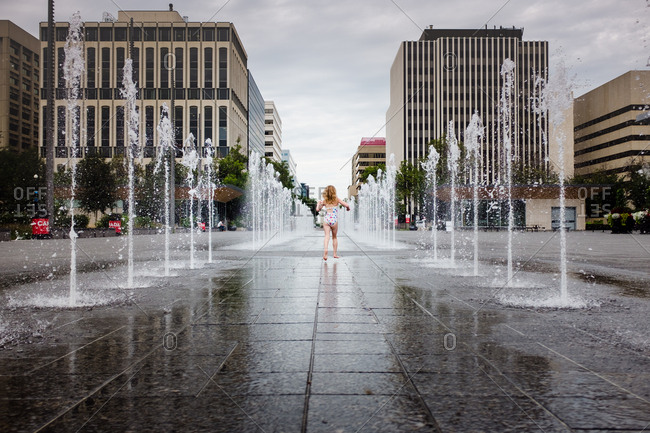 Girl in bathing suit running between city fountains on a warm day