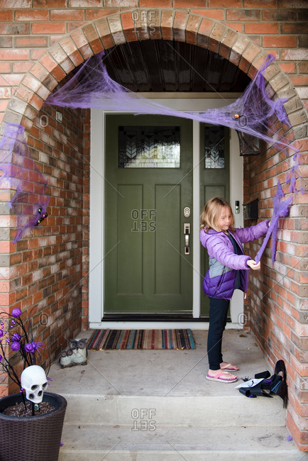 Girl decorating porch with spider webs for Halloween