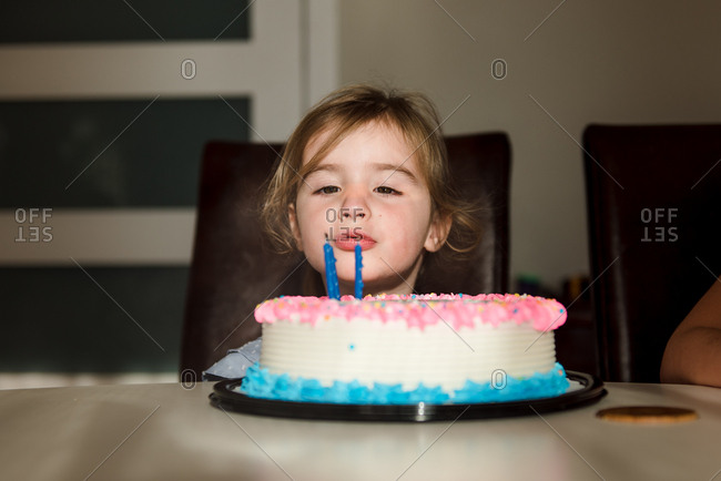 Toddler making wish on her two-year birthday cake candles