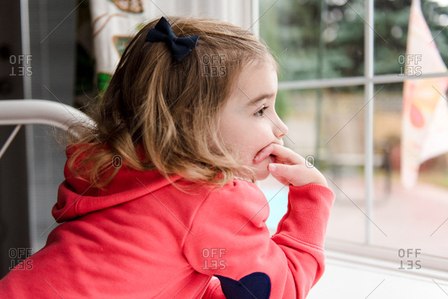 Young girl leaning on windowsill to look outside