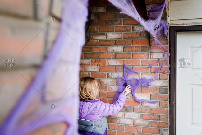 Girl putting on finishing touches to fake spider web Halloween decorations