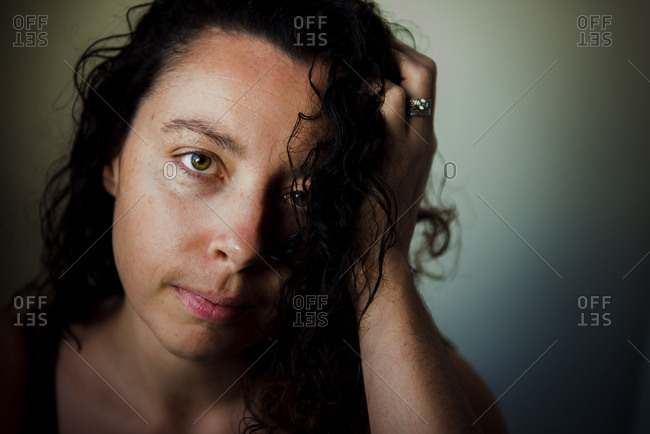 Somber woman with freckles and dark curls