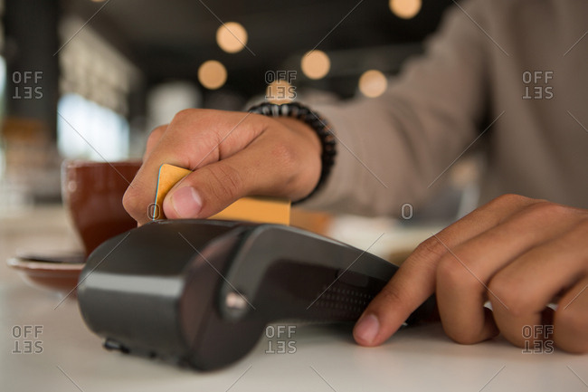 Man making payment through debit card in cafeteria