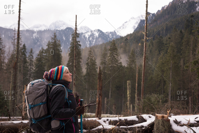 Thoughtful senior woman standing with backpack and hiking pole during winter