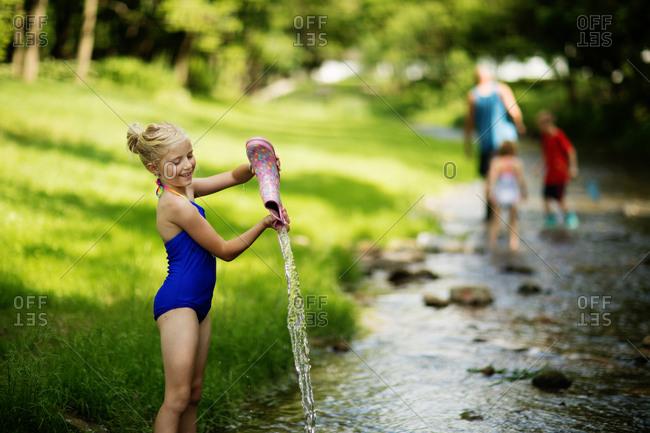 Girl pouring water out of boot in creek