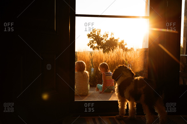 Sisters sitting on front porch, dog watching