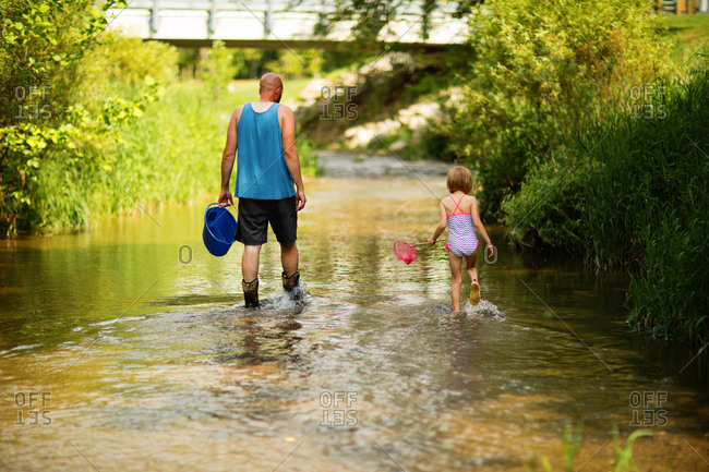 Girl and father walking through creek