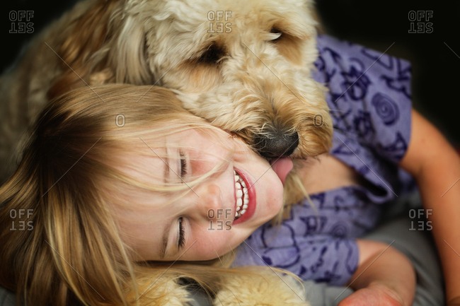 Girl with dog laughing