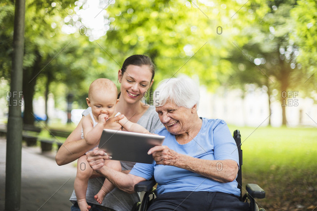 Grandmother- daughter and granddaughter having fun with tablet in a park