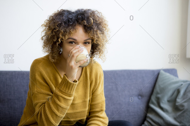 Portrait of young woman sitting on couch at home drinking
